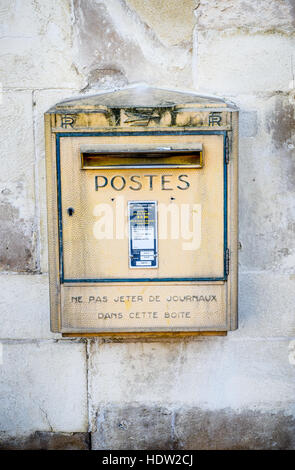 Post Box or Mail Box. Postes Box from La Poste in France mounted on a stone wall in a town centre. - Stock Photo