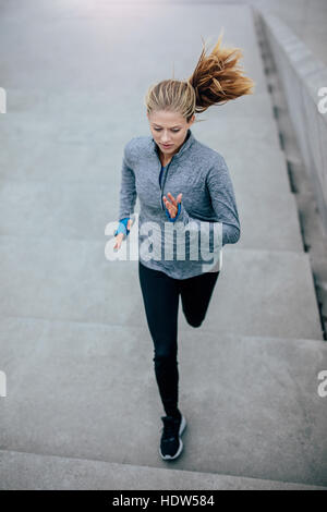 Top view shot of health conscious woman running upstairs on steps. Fitness model doing running workout. - Stock Photo