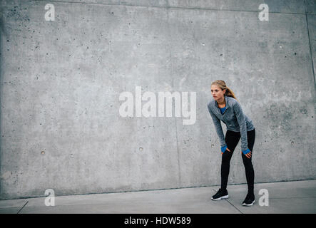 Female runner standing bent over and catching her breath after a running session in city. Young sports woman taking - Stock Photo