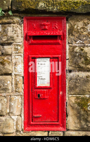 Iconic and traditional Victorian era red letter Royal Mail postbox post box with VR inset into a brick wall. - Stock Photo