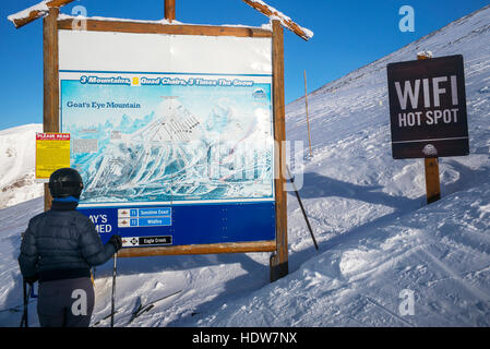 A skier stands looking at a map of the Sunshine Village ski resort with a wifi hot spot sign beside it, Banff National - Stock Photo