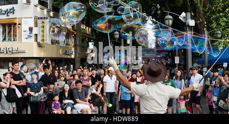 Spectators watch a street performer make bubble art with long wands; Seoul, South Korea - Stock Photo