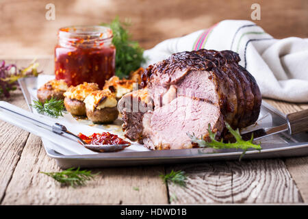 Homemade rib-eye boneless roast beef with stuffed mushrooms on baking sheet - Stock Photo