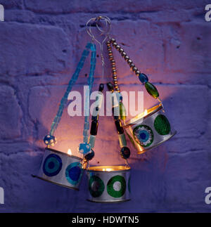 Close-up of home made tin hanging lanterns suspended by beading - Stock Photo