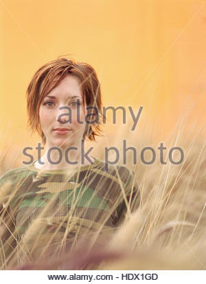 Caucasian woman standing in tall grass - Stock Photo