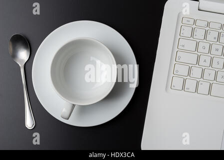 Empty coffee cup next to laptop on dark natural wooden desk. - Stock Photo