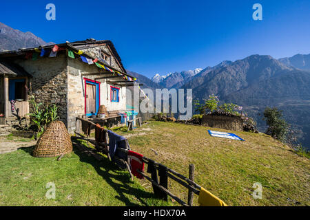 Farmers house in agricultural landscape with high mountains in the distance - Stock Photo