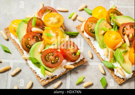 Healthy rye crisp bread toast  with cream cheese, fresh avocado, cherry tomatoes and pine nuts - Stock Photo