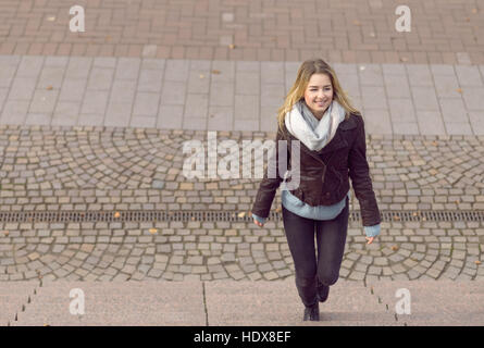 Smiling trendy young woman walking up steps outdoors with copyspace - Stock Photo