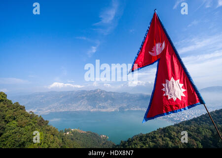 The nepali national flag is weaving high above the Phewa Lake and Pokhara, Annapurna mountains in the distance - Stock Photo