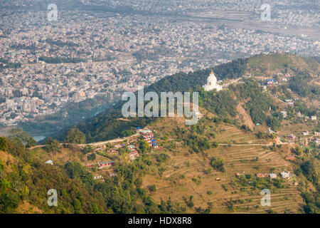 Aerial view on a local village and the World Peace Stupa, Pokhara and some mountains in the distance - Stock Photo