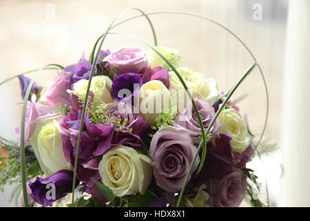 A wedding bouquet made of roses in dusky pink, magenta, and cream shades - Stock Photo