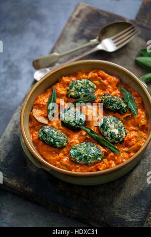 Spinach and ricotta dumplings in tomato and courgette sauce - Stock Photo