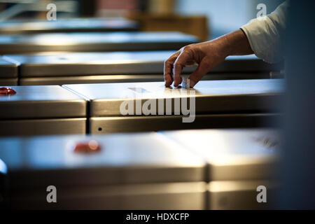 A commuter hand takes a travel ticket from a subway metro machine - Stock Photo