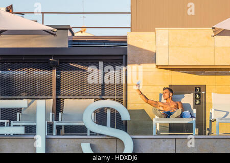 A 20s something bare-chested male on the top floor pool space of a Barcelona hotel takes selfies of himself using - Stock Photo