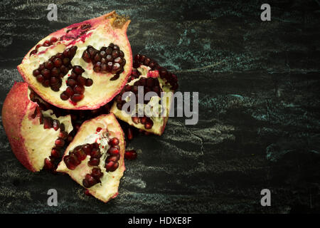 Pomegranate fruit cut in half on a dark background, showing red seeds. Healthy eating, diet or cooking concept. - Stock Photo