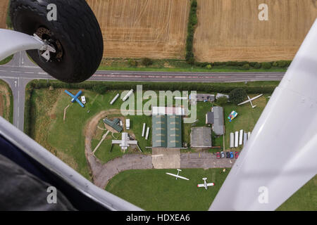 A light aircraft with the passenger door open shows an aerial view of an airfield below. - Stock Photo