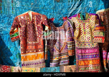 City street market with traditional clothes on the wall of Jaisalmer fort in Rajasthan, India - Stock Photo
