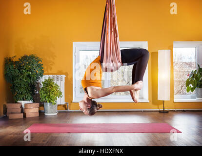 Young woman doing antigravity yoga backward bending position at studio with yellow walls - Stock Photo