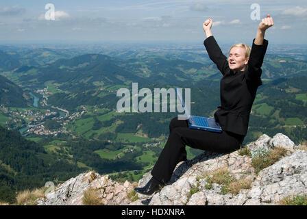 Businesswoman on a mountain peak with a laptop - Stock Photo