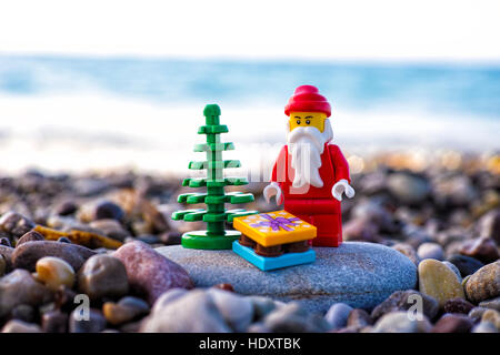 Paphos, Cyprus - November 20, 2016 Lego Santa Claus with Christmas tree and present stand on pebble beach against - Stock Photo