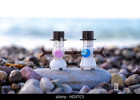 Paphos, Cyprus - November 20, 2016 Lego snowman and snowwoman stand on pebble beach against sea. - Stock Photo