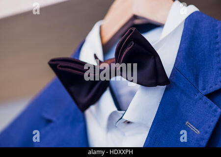 Close-up of blue jacket with bow tie on a hanger. - Stock Photo