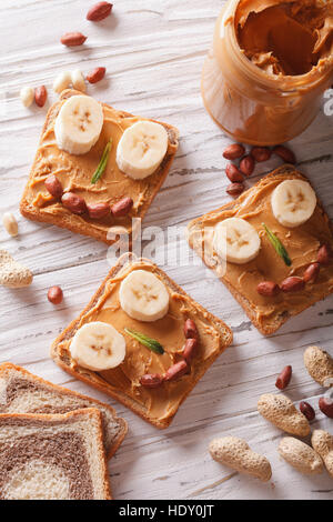 Kids sandwiches with peanut cream and banana. top view vertical - Stock Photo