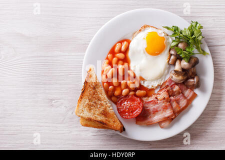 Fried egg with bacon, beans and toast on a plate. horizontal view from above - Stock Photo
