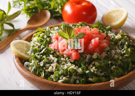 Vegetarian salad Tabbouleh close up in a wooden bowl and ingredients. horizontal - Stock Photo