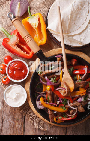 Delicious fajitas on a table in a rustic style. Vertical close-up view from above - Stock Photo