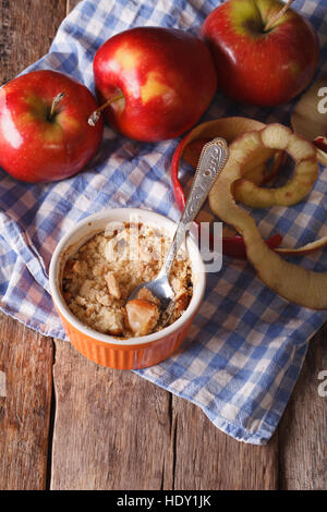 Traditional apple crumble close-up in a pot. view from above vertical, rustic style - Stock Photo
