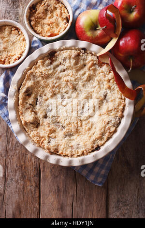 Traditional apple crisp close-up in baking dish. view from above vertical, rustic style - Stock Photo