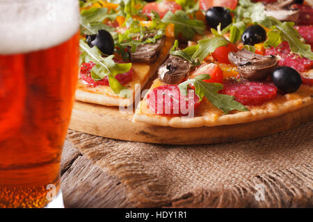 Sliced pizza with rucola and salami close-up and beer on the table. horizontal, rustic style - Stock Photo