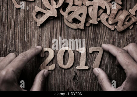 closeup of a young man forming the number 2017, as the new year, with wooden numbers, on a rustic wooden table, - Stock Photo