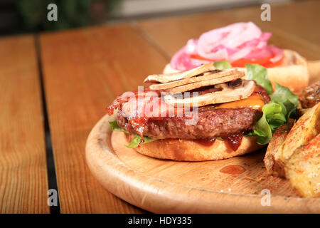 beef burger on a plate served with fried potatoes and sauces - Stock Photo