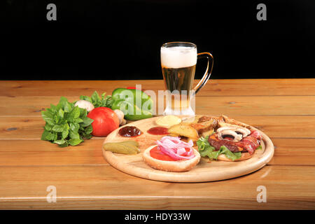 beef burger on a plate with fresh vegetables and cold glass of beer - Stock Photo
