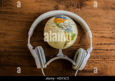Globe, headphones lie on the wooden table background. The concept of tourism, audobook, auduo guide - Stock Photo