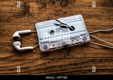 Retro compact cassette with rolls and white micro headphones on wooden table texture. Audio background - Stock Photo