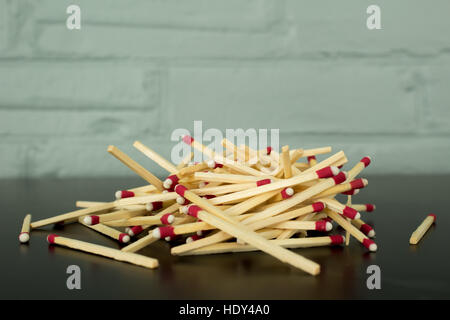 A pile of strike-anywhere matches against a blue painted brick background, with reflection on black table. - Stock Photo