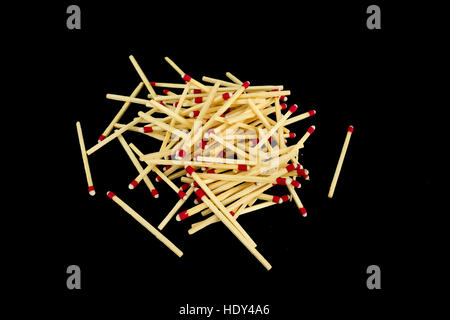 A pile of strike-anywhere matches isolated on a black background, photographed from the side - Stock Photo