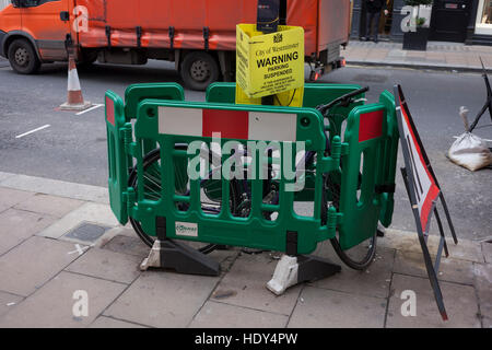A bike has been fenced in between some construction barriers and beneath a parking suspension warning sign in Bond - Stock Photo