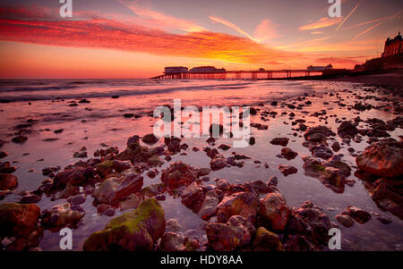 Sunrise over Cromer Pier, home to the Cromer Lifeboat Station and the Pavilion Theatre, on the Norfolk coast - Stock Photo