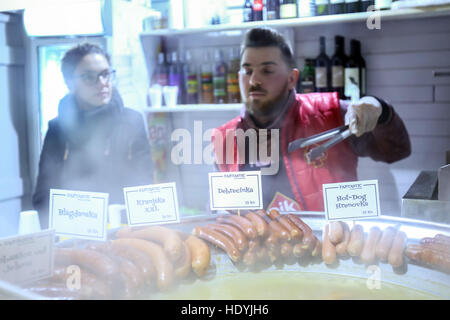 Man selling popular fast food, sausages fryed in the oil at a food stand in the upper old town Gradec, Zagreb, Croatia. - Stock Photo