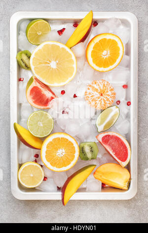 Various sliced citrus and other fruits in metal tray on ice. Top view, blank space - Stock Photo