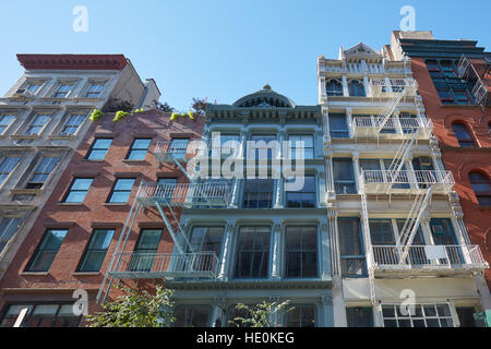 Typical houses facades with fire escape stairs, sunny day in Soho, New York - Stock Photo