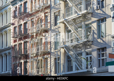 Houses facades with fire escape stairs background, sunny morning in Soho, New York - Stock Photo