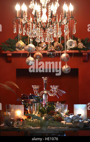 Christmas table set with baubles on a chandelier - Stock Photo