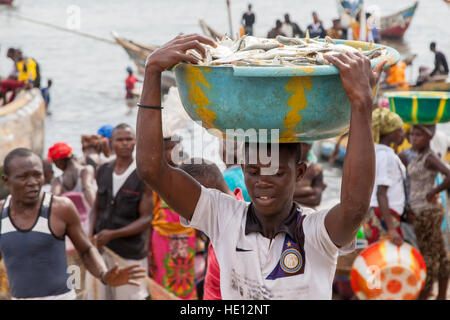 Busy traffic on beach in Tombo Harbour, Sierra Leone. Women are waiting for more fishing boats to arrive. - Stock Photo