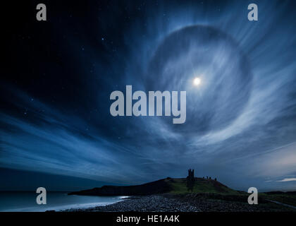 A 22° lunar halo over Dunstanburgh Castle on Northumberland coast in the UK - Stock Photo